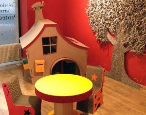 Espace enfant : cabane, arbre, table et chaises en carton