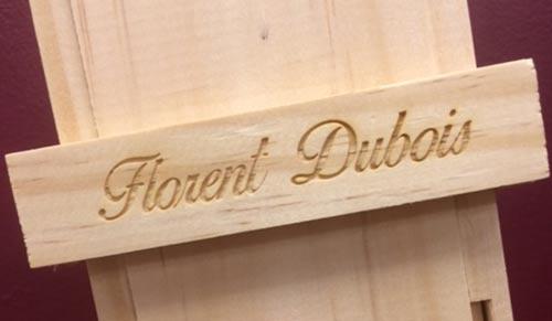 zoom sur gravure laser sur bois personnalisée sur une bouteille d'Armagnac